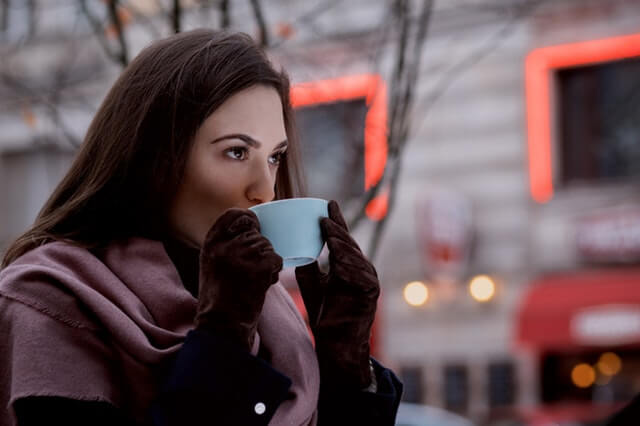 girl in gloves drinking coffee